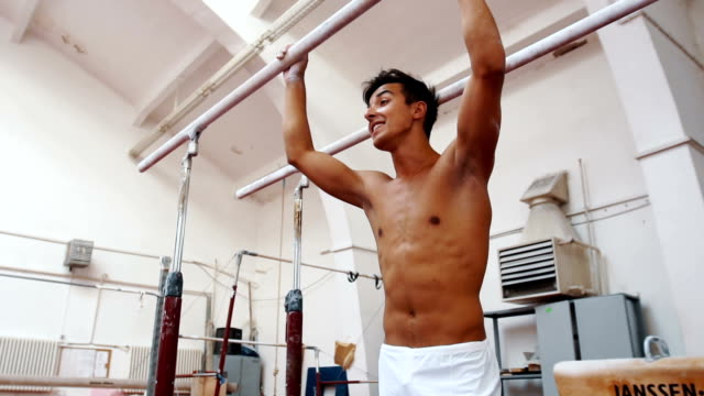 Smiling male gymnast relaxing after exercise