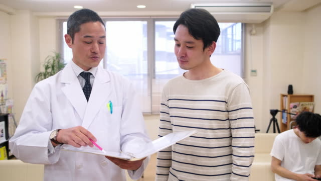 vídeos de stock e filmes b-roll de smiling male japanese doctor reassuring male patient - leste