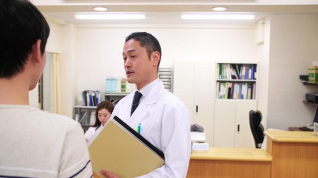 leende manlig japansk läkare lugnande manlig patient - sjuksköterskereception bildbanksvideor och videomaterial från bakom kulisserna