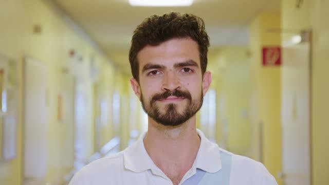 smiling male nurse standing in hospital corridor - male nurse stock videos & royalty-free footage