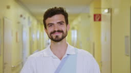 Smiling male nurse standing in hospital corridor
