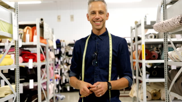 smiling male tailor with tape around neck at shop - textile industry stock videos & royalty-free footage