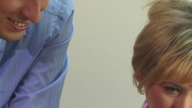 ecu, smiling man and woman working in office - 談笑する点の映像素材/bロール
