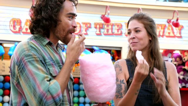 vídeos y material grabado en eventos de stock de ms smiling man feeding girlfriend cotton candy while on date in amusement park - citas románticas