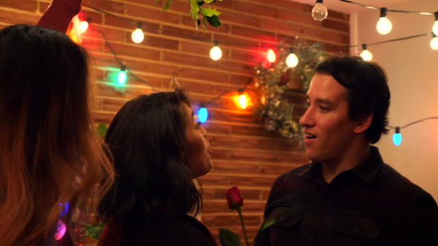 stockvideo's en b-roll-footage met ms smiling man giving girlfriend rose while kissing under mistletoe during holiday party - echte mensen