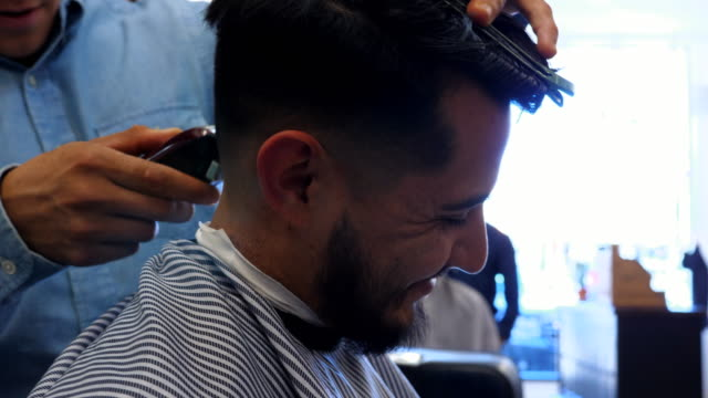 ms la smiling man having hair cut with trimmers in barber shop - hairdresser stock videos & royalty-free footage