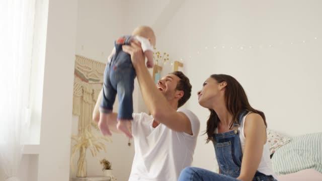 Smiling man holding aloft son sitting on woman