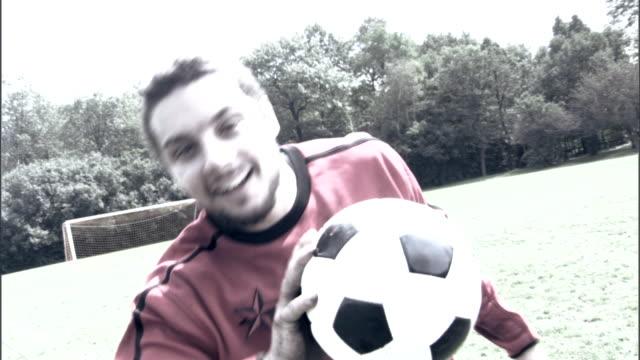 Smiling man holding soccer ball