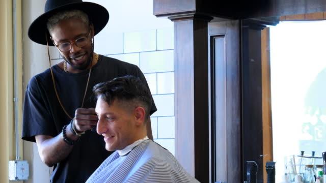 ms r/f smiling man in discussion with barber while having hair cut in barber shop - 30 34 ��r bildbanksvideor och videomaterial från bakom kulisserna