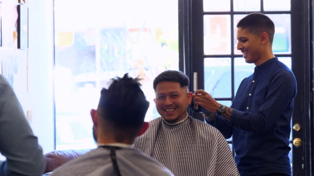 MS Smiling man in discussion with friend while having hair cut in barber shop