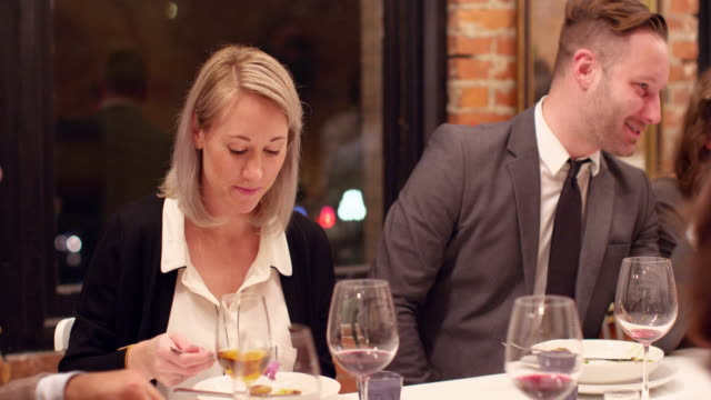 MS Smiling man in discussion with friends during dinner party