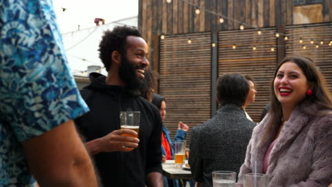 ms smiling man in discussion with friends during party at outdoor bar - 30 39 years stock videos & royalty-free footage