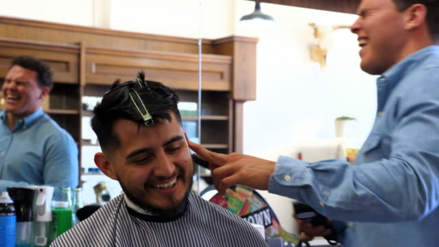 ms smiling man in discussion with laughing barber while having hair cut in barber shop - beauty salon stock videos and b-roll footage