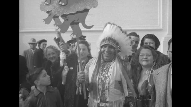 vidéos et rushes de smiling man in native american costume holding a stick featuring a wooden elephant wearing a tutu, followed by a woman carrying another wooden... - tutu