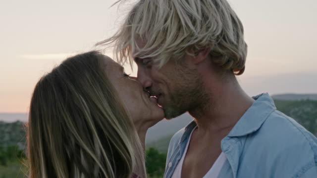stockvideo's en b-roll-footage met glimlachende mens die meisje tijdens zonsondergang kust - gezicht aan gezicht