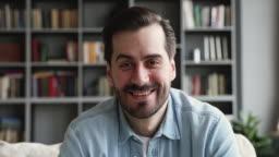 Smiling man look at camera talk make videocall at home