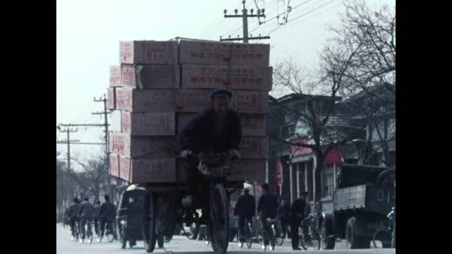 smiling man pedals overloaded tricycle in beijing; 1973 - tricycle stock videos & royalty-free footage