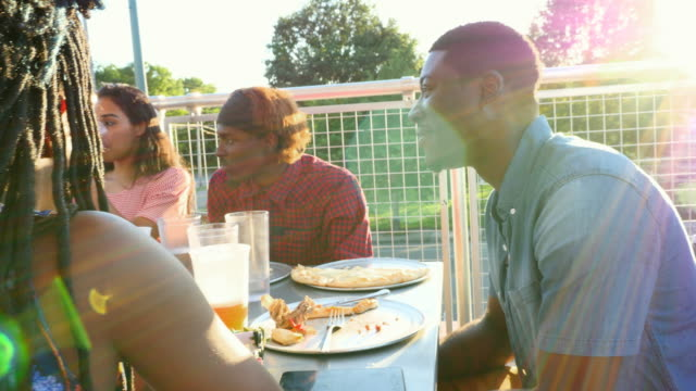 MS Smiling man sharing pizza with friends at outdoor table on summer evening