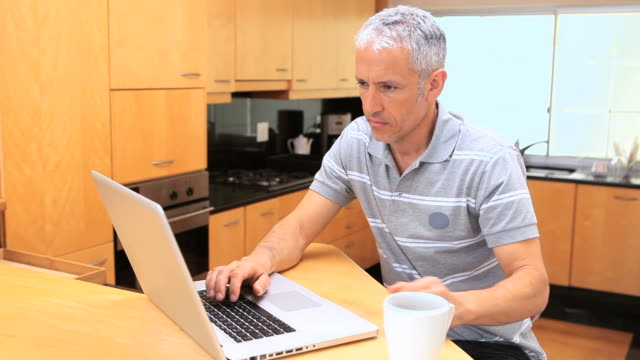 Smiling man typing on his laptop