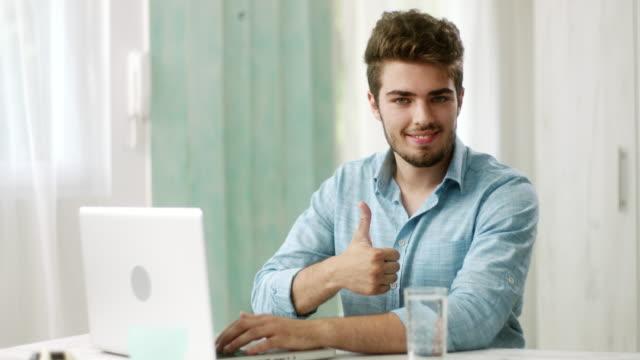 vidéos et rushes de homme taper sur ordinateur portable, sensibilisation de l'opinion et montrant les pouces vers le haut à caméra souriant - pouce levé