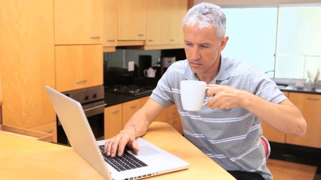vídeos de stock, filmes e b-roll de smiling man using a laptop - cabelo branco