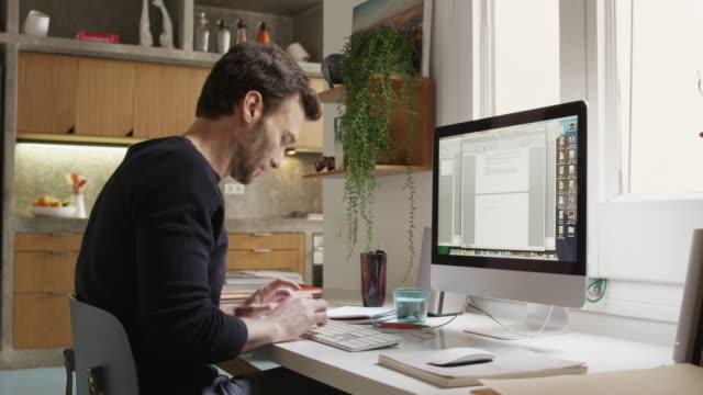 vídeos y material grabado en eventos de stock de sonriente hombre con ayuda de computadora en escritorio de oficina en casa - oficina pequeña
