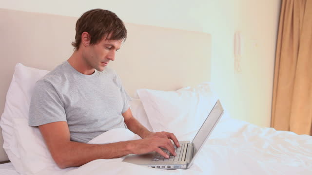smiling man using his laptop - nur junge männer stock-videos und b-roll-filmmaterial