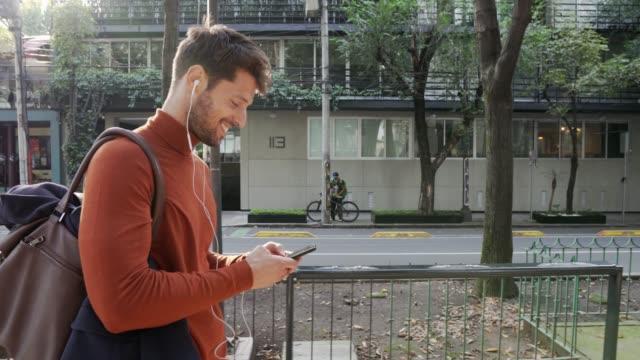 vidéos et rushes de homme de sourire utilisant le téléphone portable. - bonne nouvelle