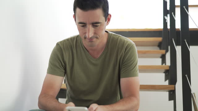 smiling man using smart phone while sitting on staircase at home - 35 39 years stock videos & royalty-free footage