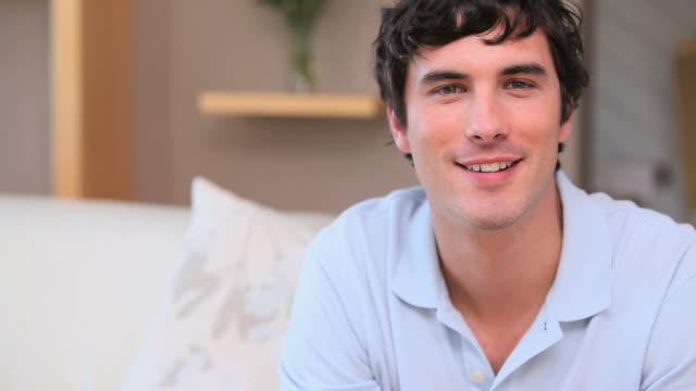 smiling man watching the television - nur junge männer stock-videos und b-roll-filmmaterial