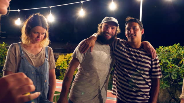 stockvideo's en b-roll-footage met pan smiling man with arm around friend during backyard party on summer evening - friendship