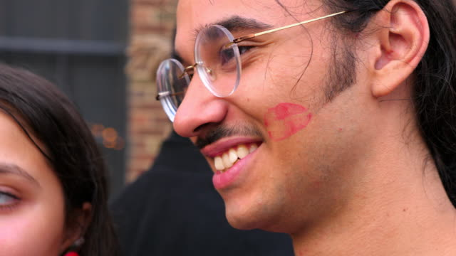 cu smiling man with lipstick kiss on cheek in discussion with girlfriend - lipstick kiss stock videos and b-roll footage
