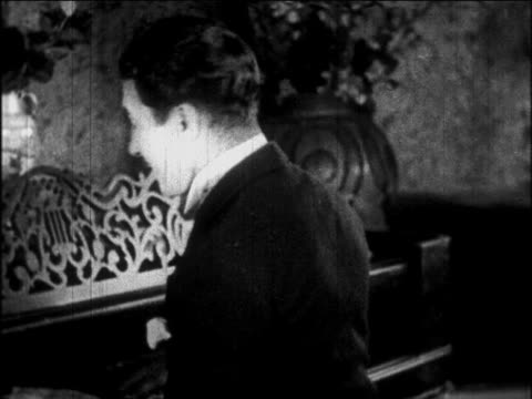 vídeos de stock e filmes b-roll de b/w 1926 smiling man with mustache playing piano + turning to look behind him / newsreel - piscar
