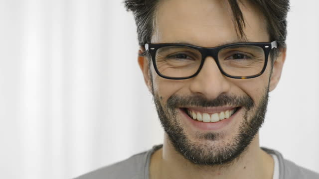 uomo sorridente con specifiche - uomini video stock e b–roll