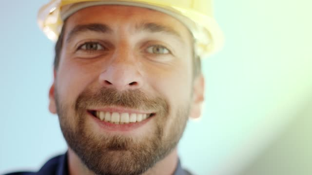 smiling man working on blueprints - examining stock videos & royalty-free footage