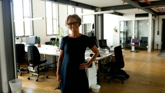 smiling mature businesswoman standing at office - hand on hip stock videos & royalty-free footage