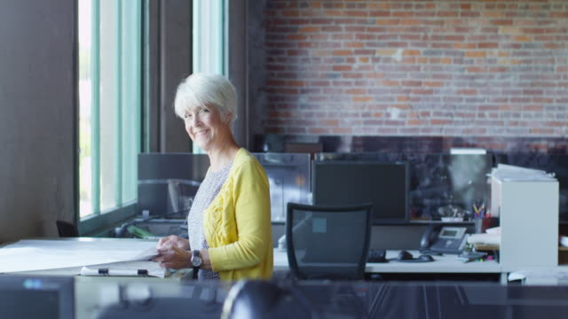 MS Smiling mature businesswoman standing in office looking over project plans