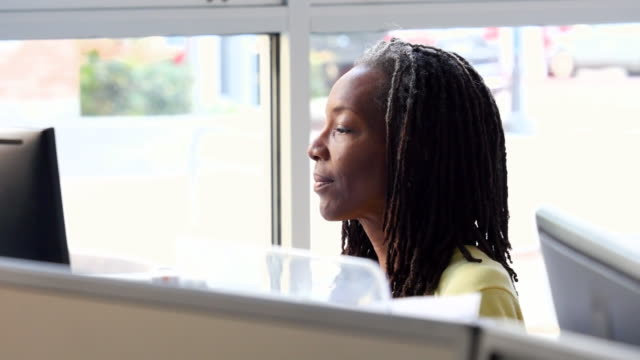 ms smiling mature businesswoman working on computer at workstation in office - dreadlocks stock videos & royalty-free footage