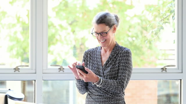 MS Smiling mature businesswoman working on smartphone in office