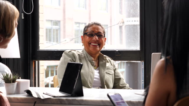 ms smiling mature businesswomen in planning meeting with colleagues in small office - small office stock videos & royalty-free footage