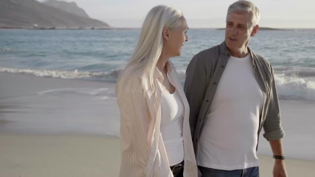 vídeos y material grabado en eventos de stock de sonriendo pareja madura caminando en la playa en verano - pareja madura