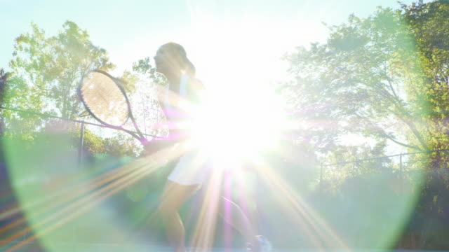 ms tu smiling mature female tennis player playing at net during early morning tennis match - athleticism stock videos & royalty-free footage