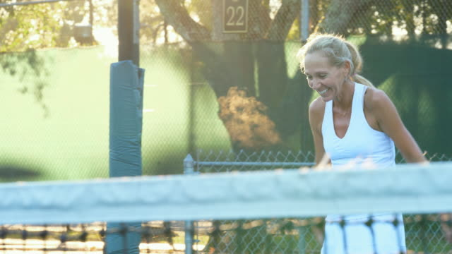 ms smiling mature female tennis player playing at net during early morning tennis workout - tennis stock videos & royalty-free footage