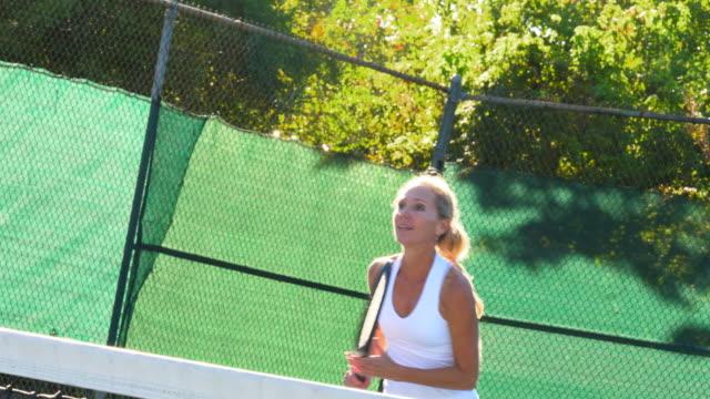 stockvideo's en b-roll-footage met ms tu smiling mature female tennis player practicing overhead shots during early morning tennis workout - paardenstaart haar naar achteren
