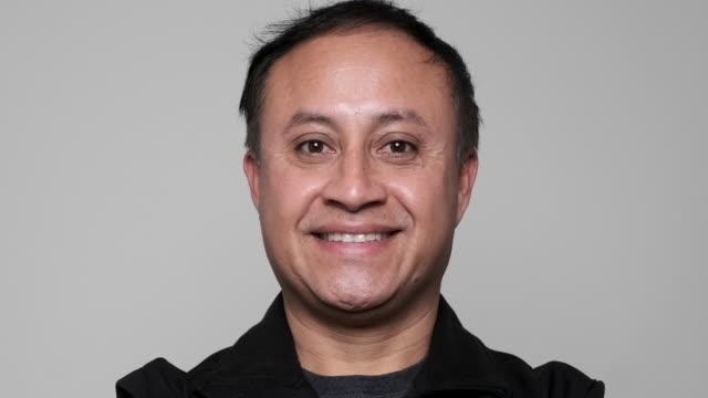 vídeos de stock e filmes b-roll de smiling mature hispanic man looking at the camera - emigração e imigração