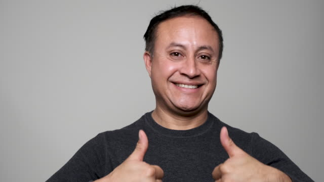 smiling mature hispanic man posing with his both thumbs up - ok sign stock videos & royalty-free footage