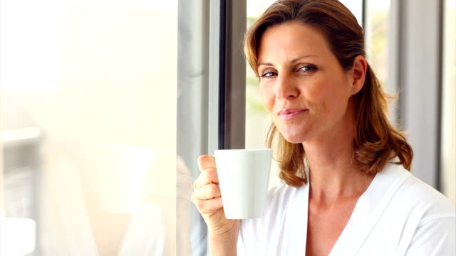 smiling mature lady holding a coffee cup - femininity stock videos & royalty-free footage