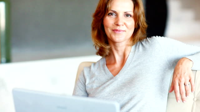 smiling mature lady with her laptop - sitting stock videos & royalty-free footage
