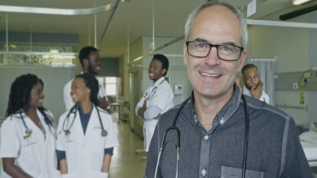 smiling mature male doctor with medical students - hospital leadership stock videos & royalty-free footage