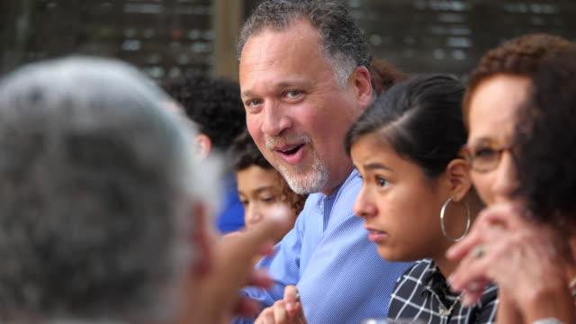 ms smiling mature man in discussion with senior man during outdoor dinner party - mellanstor grupp av människor bildbanksvideor och videomaterial från bakom kulisserna